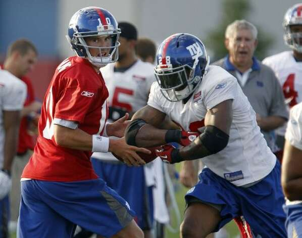 New York Giants quarterback Eli Manning (10) hands off to New York Giants running back Danny Ware (28) at the New York Giants practice facility as the Giants have their first night of training camp in East Rutherford, NJ  7/30/11 (William Perlman/The Star-Ledger) Sent DIRECT TO SELECTS Saturday, July 30, 2011 20:55:25 2452 1928 (SL)