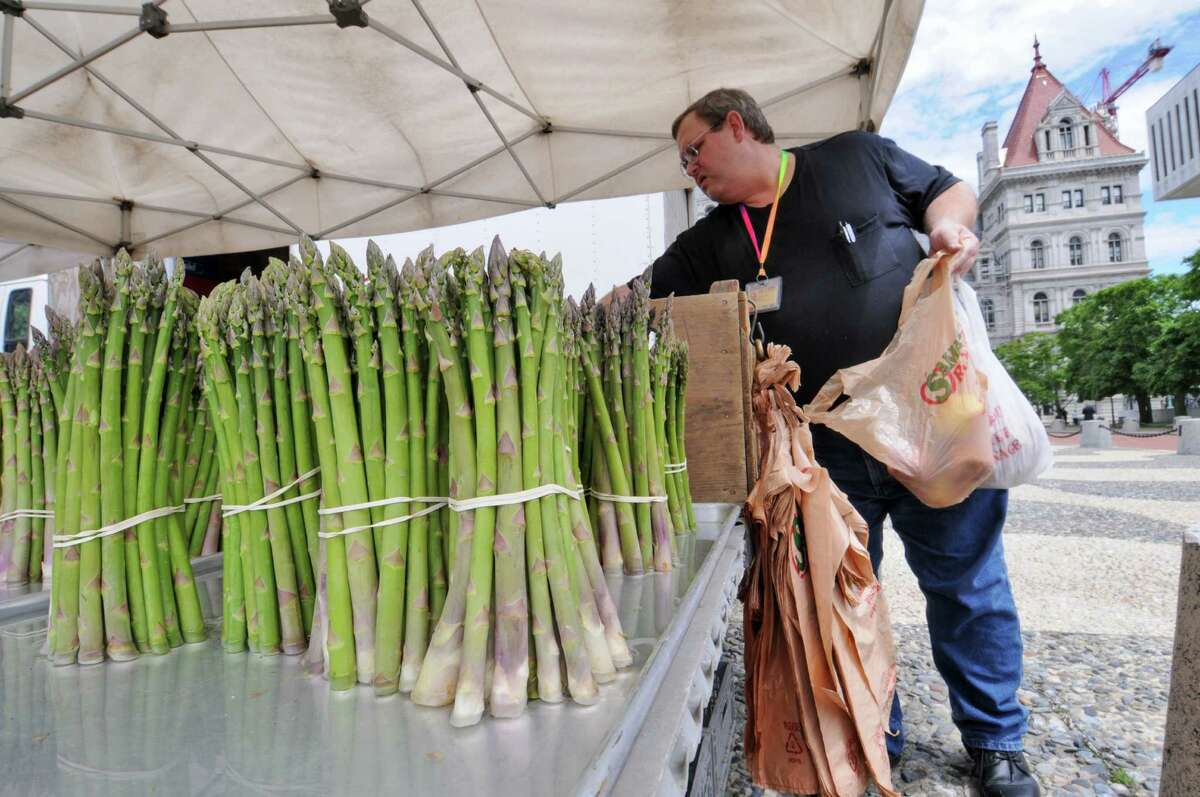 Steven Smith of Menands shops at the tables of Samascott Orchards, of Kinderhook, at the farmers' market on the Empire State Plaza on Wednesday June 6, 2012 in Albany, NY. Access to farmer's markets would improve under a bipartisan farm bill that U.S. Senators Charles Schumer and Kirsten Gillibrand are working on .(Philip Kamrass / Times Union )