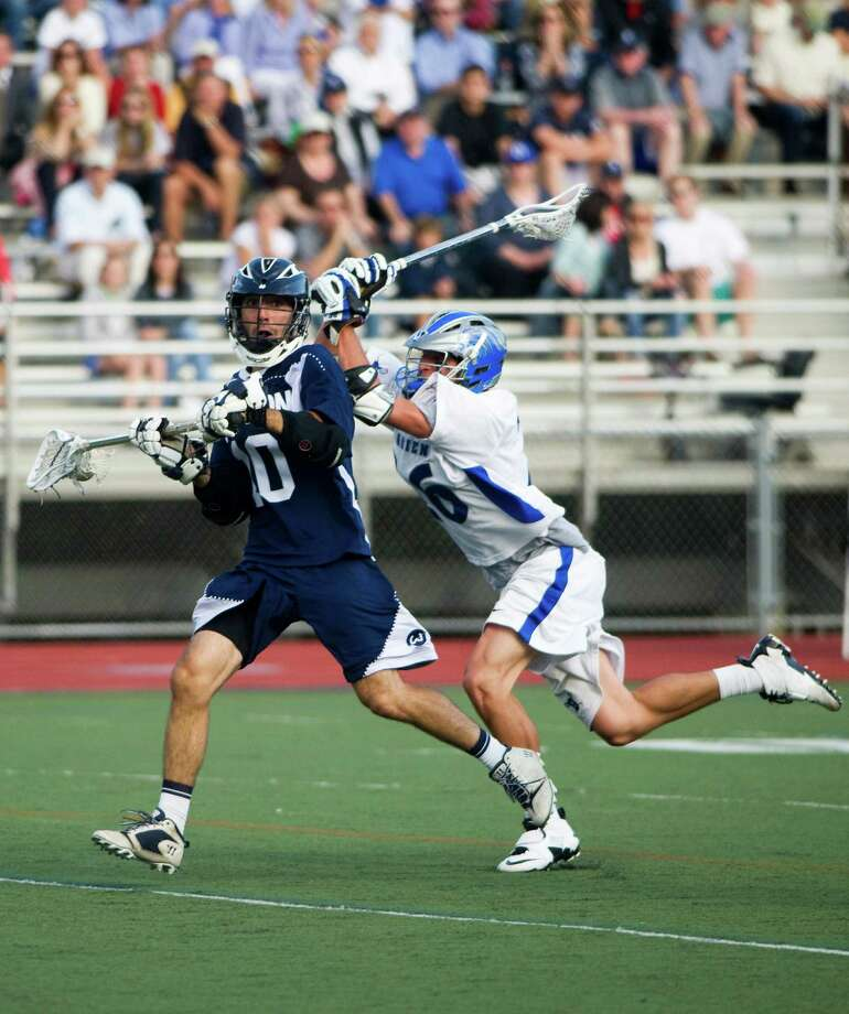 Wilton's Rob Marino looks to pass as Darien's Peter Gesualdi tries to put a stop to him as Wilton and Darien High Schools face off in the Class M boys lacrosse semifinals at Brien McMahon in Norwalk, Conn., June 6, 2012.  Darien won to advance. Photo: Keelin Daly / Stamford Advocate