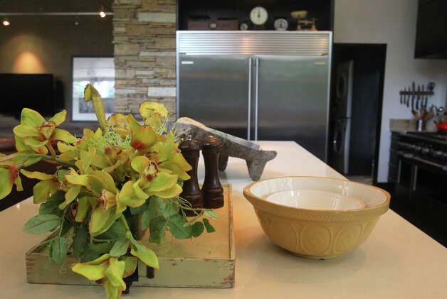 Decorative and functional accents are on the caesarstone countertop of an island in the kitchen of Cindi and Barney Dishron. A stainless Electrolux refrigerator is in the background. (Monday May 7, 2012) John Davenport/San Antonio Express-News Photo: JOHN DAVENPORT, SAN ANTONIO EXPRESS-NEWS / SAN ANTONIO EXPRESS-NEWS (Photo can be sold to the public)