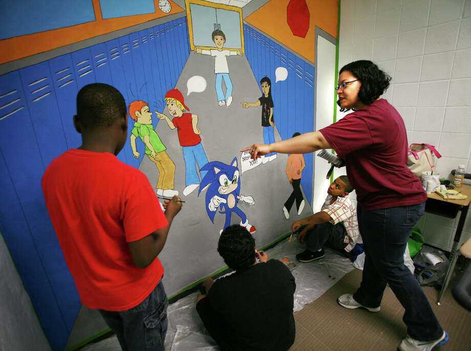 From left; Students Carl Augustin, 10, Ralph Maselli, 12, and Brandon Powell, 11, paint an anti-bullying mural under the direction of Powell's mother, Alicia Cobb, at Eli Whitney Elementary School in Stratford on Thursday, June 7, 2012. Photo: Brian A. Pounds / Connecticut Post