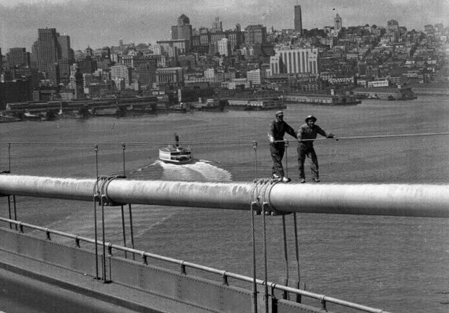 Nov. 17, 1948: Bay Bridge painters on one of the western span suspension cables. There were no nets, and between 24 and 28 Bay Bridge workers died.