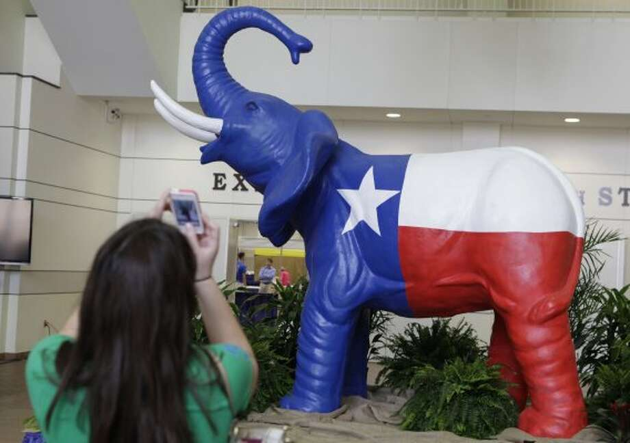 Sarah Mercer, of San Antonio, makes a photo of a Texas flag elephant statue during the set up before the start of the Texas Republican Convention Wednesday, June 6, 2012, in Fort Worth, Texas.  The Texas GOP convention starts tomorrow and runs through Saturday. (LM Otero / Associated Press)