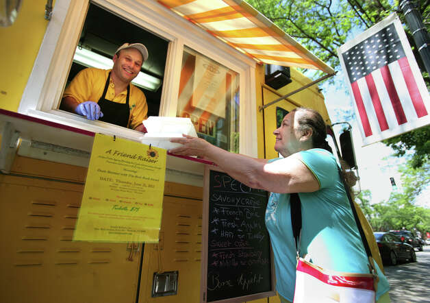 Christophe Ensenat hands Anna Withers of Fairfield a couple of dessert crepes to go at Christophe's Crepes truck in downtown Fairfield, Conn. on Thursday, June 7, 2012. Photo: Brian A. Pounds / Connecticut Post