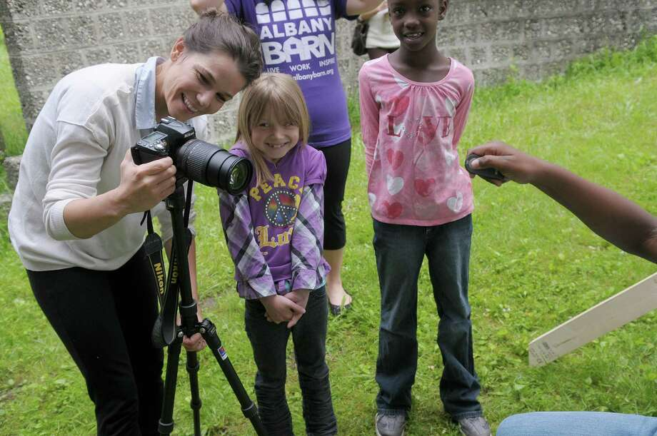 Sasha Sicurella, left, adjusts her camera as second graders, Destiny Perlmutter, center, and Zhamaije Monroe look on at Arbor Hill Elementary School on Wednesday, June 6, 2012 in Albany, NY.  Sasha Sicurella, an artist and photographer was at the school helping children take self portraits as part of her on-going international project.  The children sit in front of a backdrop and then trigger the camera with a handheld remote.  (Paul Buckowski / Times Union) Photo: Paul Buckowski / 00017951A