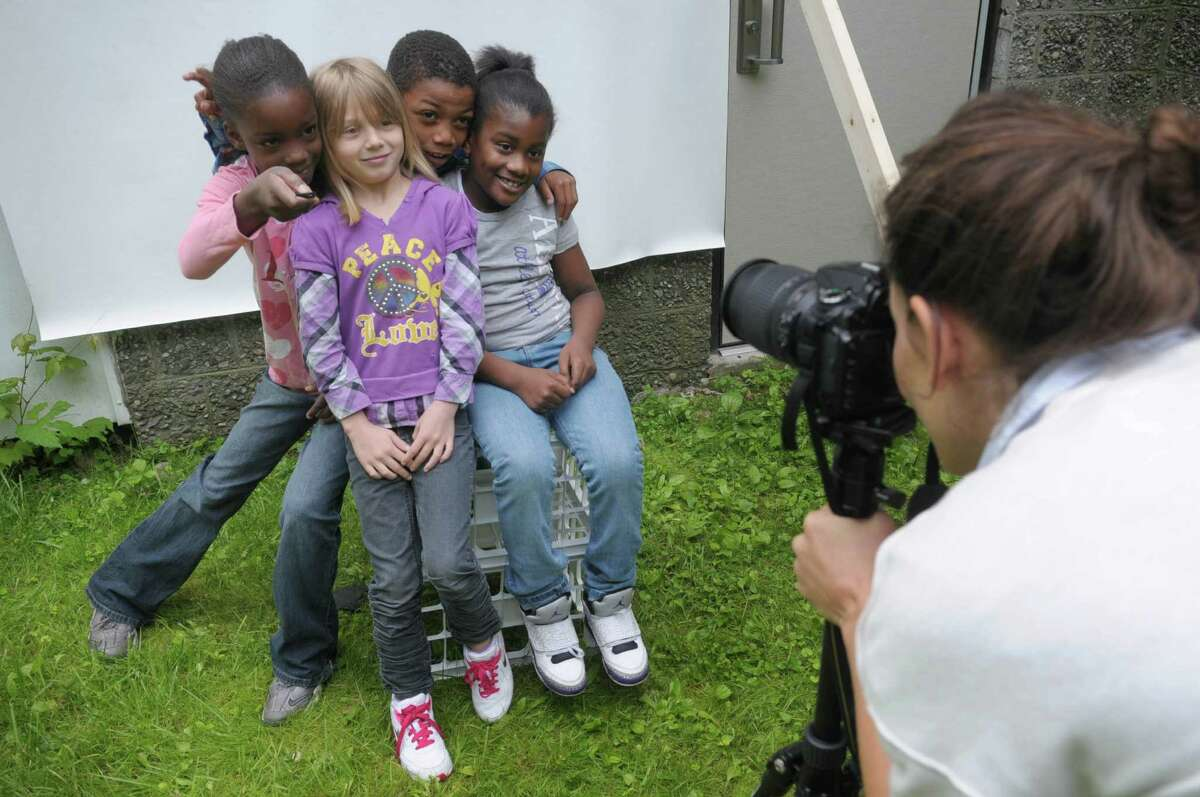 Sasha Sicurella, right, adjusts her camera as second graders, from left, Zhamaije Monroe, Destiny Perlmutter, Kygii Humes and Mavihaa Chandler pose together at Arbor Hill Elementary School on Wednesday, June 6, 2012 in Albany, NY. Sasha Sicurella, an artist and photographer was at the school helping children take self portraits as part of her on-going international project. The children sit in front of a backdrop and then trigger the camera with a handheld remote. (Paul Buckowski / Times Union)