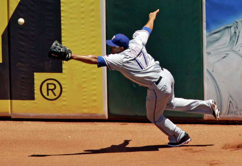Texas Rangers right fielder Nelson Cruz chases the ball as it bounces off the outfield wall on a triple by Oakland Athletics' Coco Crisp during the fourth inning of a baseball game on Thursday, June 7, 2012, in Oakland, Calif. Photo: AP