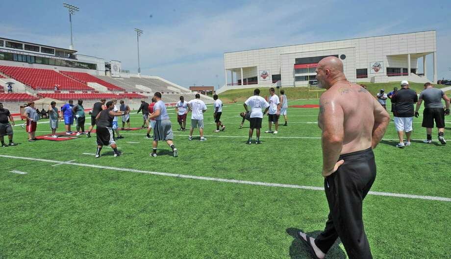 Lamar University offensive line coach Dennis McKnight, right, watches as the players run through drills.  High school offensive and defensive linemen participated in a football camp at Lamar University Thursday June 7, 2012. Dave Ryan/The Enterprise