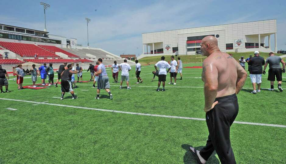 Lamar University offensive line coach Dennis McKnight, right, watches as the players run through dri