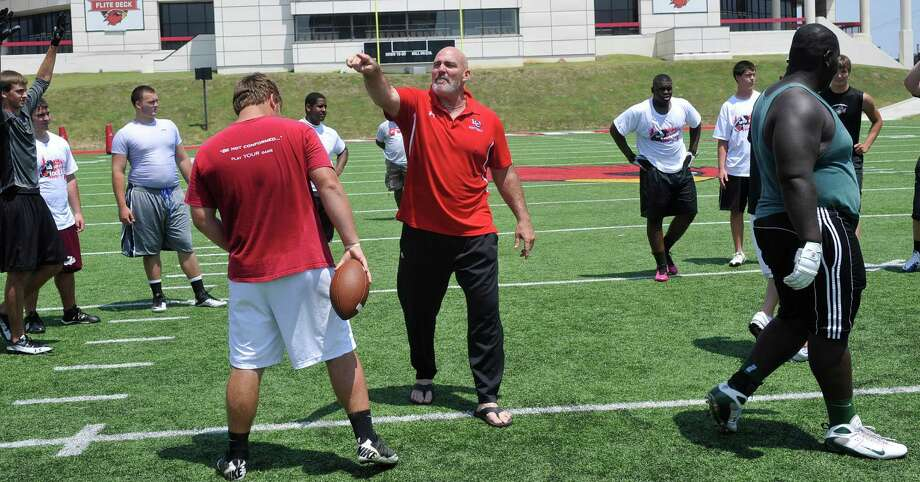 Lamar University offensive line coach Dennis McKnight, center, gives directions to the players as they run through drills near the end of their morning.  High school offensive and defensive linemen participated in a football camp at Lamar University Thursday June 7, 2012. Dave Ryan/The Enterprise