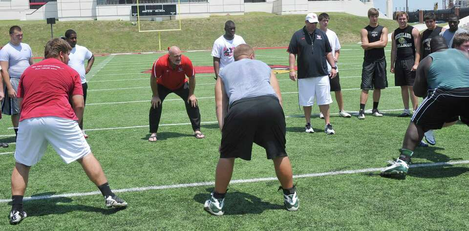 Lamar University offensive line coach Dennis McKnight, left center, watches the players as they run