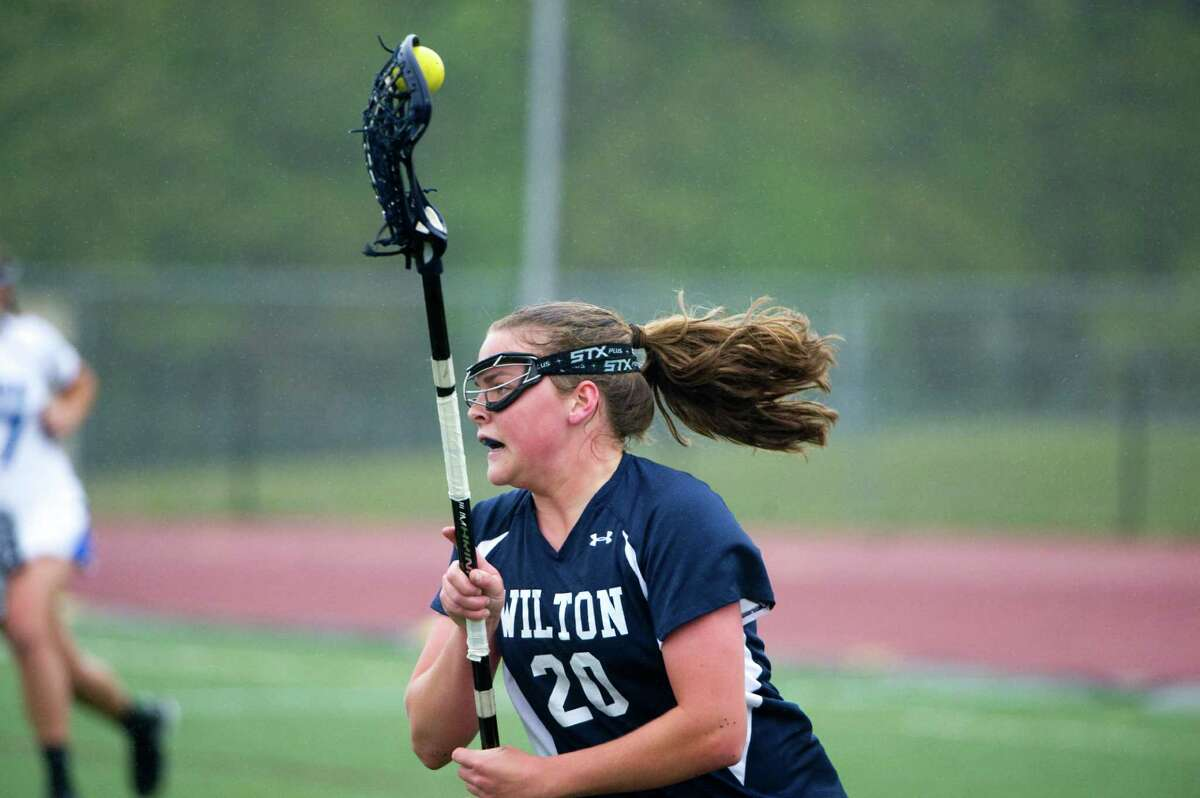 Wilton's Megan Boepple carries as Darien High School hosts Wilton in a girls lacrosse game in Darien, Conn., April 26, 2012.