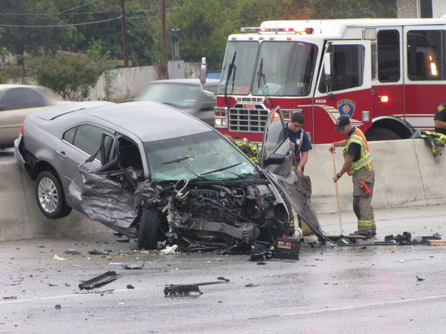A silver car is lodged between Loop 410 and a concrete barrier after it was struck head-on by a wrong-way driver in 2010. Photo: Express-News File Photo / emoravec@express-news.net