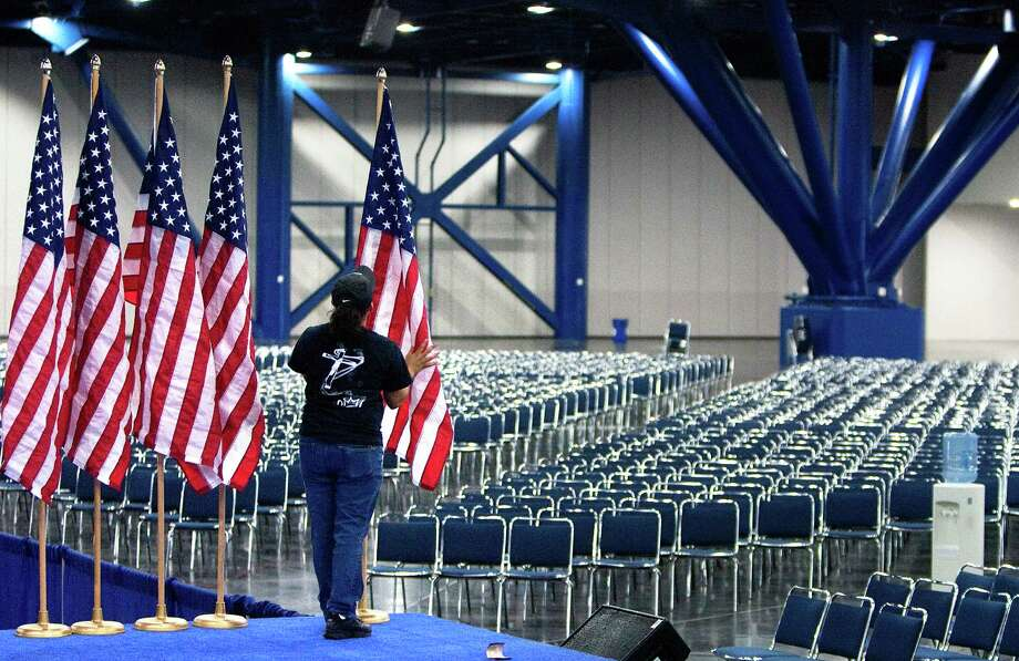 Risa Estrada prepares American flags that will line the stage during the 2012 Texas Democratic Party State Convention held at the George R. Brown Convention Center Thursday, June 7, 2012, in Houston. Photo: Cody Duty, Houston Chronicle / © 2011 Houston Chronicle