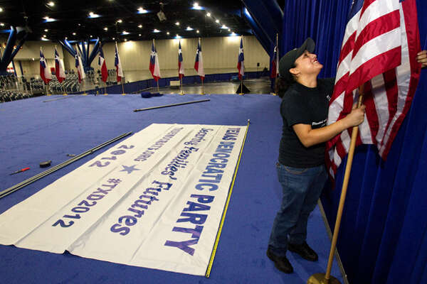 Risa Estrada prepares Texas flags and American flags that will line the stage during the 2012 Texas Democratic Party State Convention held at the George R. Brown Convention Center Thursday, June 7, 2012, in Houston.
