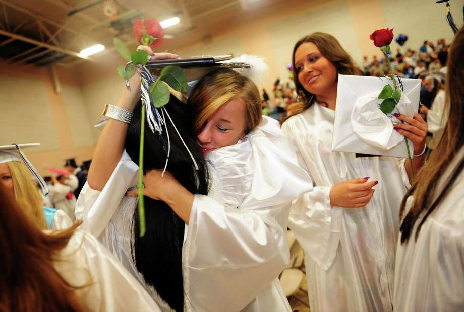 Graduate Sabina Gul hugs friend Tayshmara Martinez Santiago following Ansonia High School's commencement ceremony Thursday, June 7, 2012 at the school in Ansonia, Conn. Photo: Autumn Driscoll / Connecticut Post