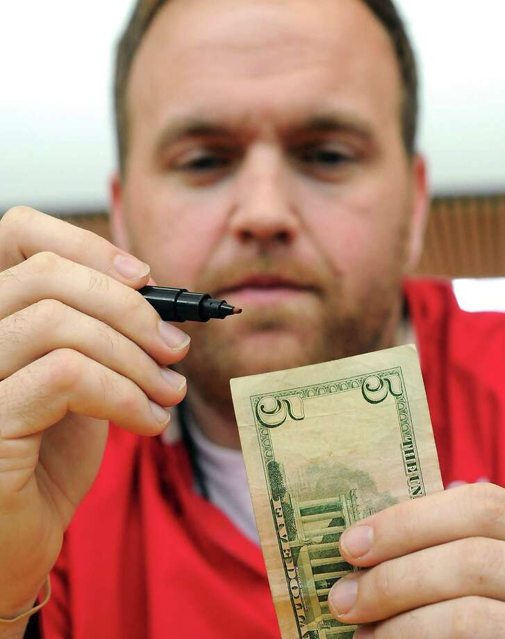 McGovern-Stella Link Library employee Patrick Atkins uses a special pen to check a $5 bill for authenticity. Photo: Dave Rossman / © 2012 Dave Rossman