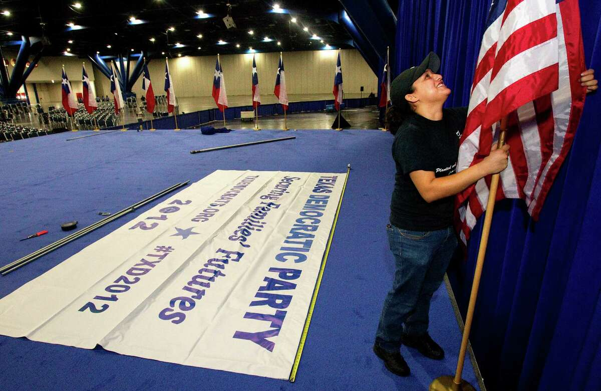 Risa Estrada sets up flags at the Texas Democratic Party State Convention at the George R. Brown Convention Center.