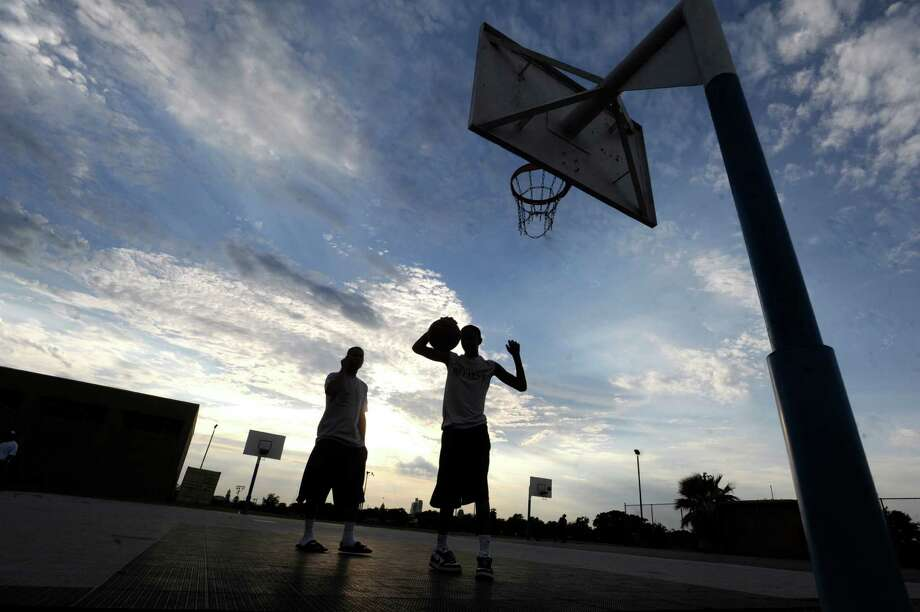 Young men play basketball outside of the Davis-Scott YMCA on Thursday, June 7, 2012. Many of the young people that play on these courts will participate in the San Antonio Eastside Promise Neighborhood Midnight Basketball League. Photo: Billy Calzada, San Antonio Express-News / © 2012 San Antonio Express-News