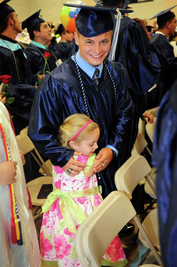 Graduate Chris Nihill's six-year-old cousin, Emily Frey, runs up to give him a hug during Ansonia High School's commencement exercises Thursday, June 7, 2012 at the school in Ansonia, Conn. Photo: Autumn Driscoll / Connecticut Post