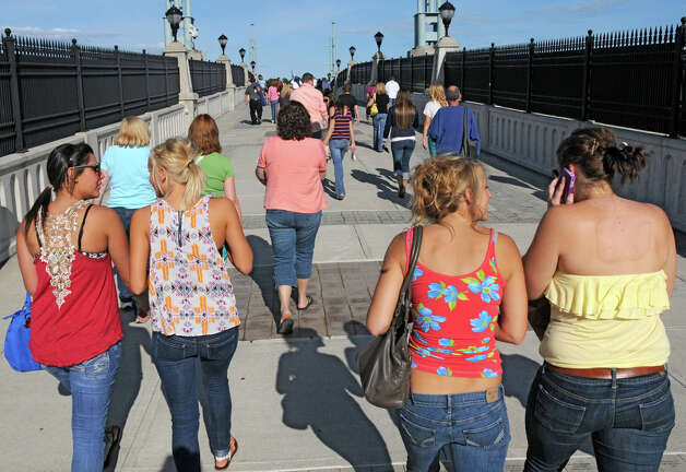 Music lovers cross the Hudson River Way pedestrian bridge to listen to Dave Mason of Traffic with the Emerald City Band as the two bands kick off the 2012 season of Alive at Five at the Corning Preserve on June 7, 2012 in Albany, N.Y.  (Lori Van Buren / Times Union) Photo: Lori Van Buren