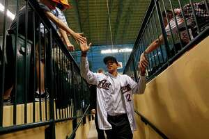 Carlos Correa high-fives fans as he walks into the tunnel on Thursday, June 7, 2012, in Houston.  The Astro's No. 1 draft pick, Carlos Correa from the Puerto Rico  Baseball Academy, singed today at Minute Maid Park.