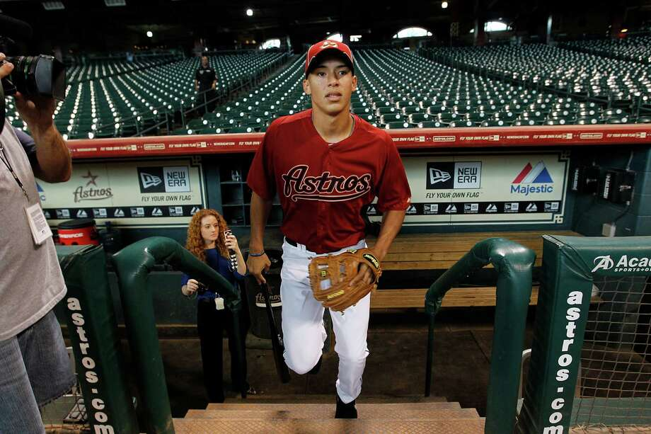 Carlos Correa walks out of the dugout for the first time as he joins the team for batting practice on Thursday, June 7, 2012, in Houston.  The Astro's No. 1 draft pick, Carlos Correa from the Puerto Rico  Baseball Academy, singed today at Minute Maid Park. Photo: Mayra Beltran, Houston Chronicle / © 2012 Houston Chronicle