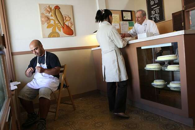 Assistant Louie Sehgal (left) cutting fish string as cheesecake maker Sam Zanze talks with a customer at Zanze's cheesecake in San Francisco, California, on Thursday, May 31, 2012.  Fish string is placed on the cheesecake boxes for cutting pieces. Photo: Liz Hafalia, The Chronicle