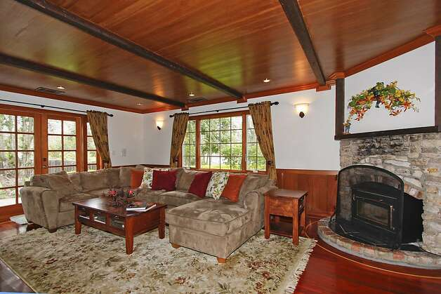 The living room boasts a stone fireplace, a beamed wooden ceiling and French doors that lead outside. Photo: Terrace Associates, Blockshopper