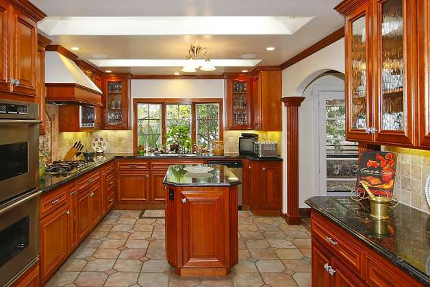 A large eat-in kitchen with granite countertops and a center island has stainless steel appliances, glass-front cabinetry and large skylights. Photo: Terrace Associates, Blockshopper