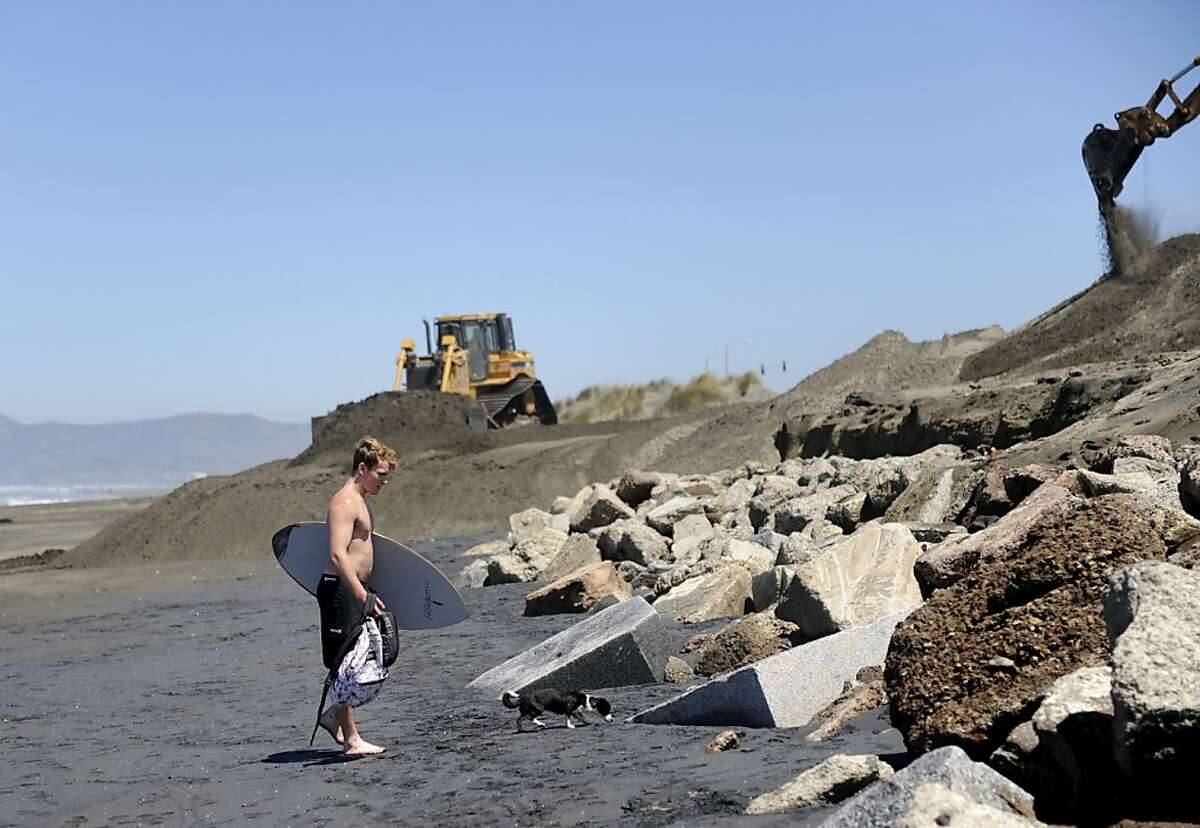 Dylan Phillipy sets his belongings on an old mausoleum near the intersection of Rivera Street and the Great Highway on Ocean Beach, where tombstones were uncovered by wind and erosion on Thursday, June 7, 2012 in San Francisco, Calif.