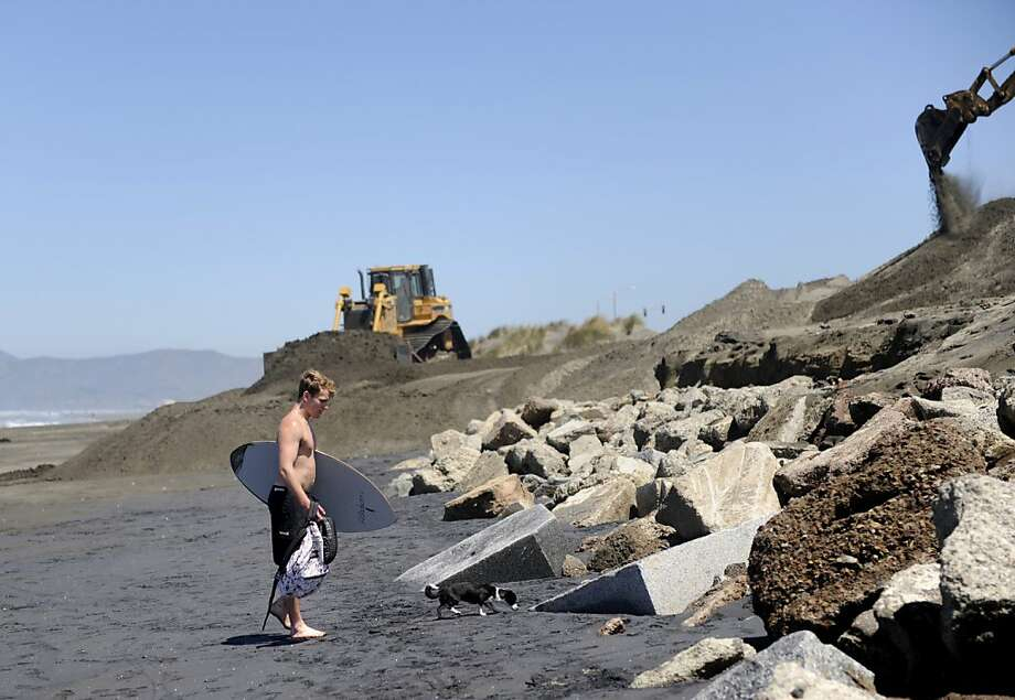 Dylan Phillipy sets his belongings on an old mausoleum near the intersection of Rivera Street and the Great Highway on Ocean Beach, where tombstones were uncovered by wind and erosion on Thursday, June 7, 2012 in San Francisco, Calif. Photo: Megan Farmer, The Chronicle