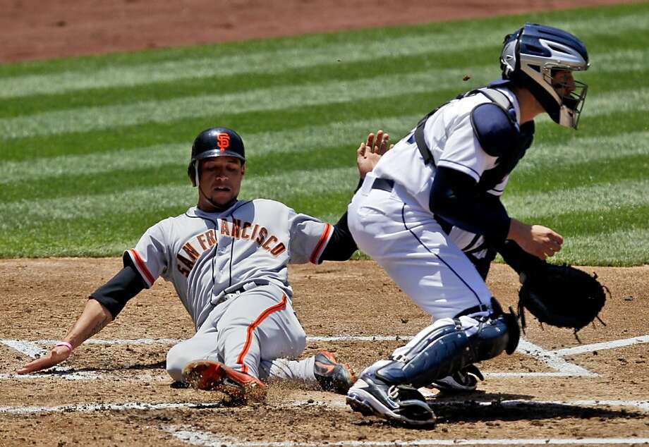 San Francisco Giants' Gregor Blanco, left, scores as San Diego Padres catcher John Baker awaits the tardy throw during the second inning of a baseball game, Thursday, June 7, 2012, in San Diego. (AP Photo/Lenny Ignelzi) Photo: Lenny Ignelzi, Associated Press
