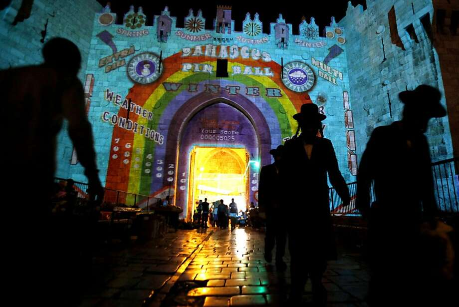 Israelis and Palestinians walk by Jerusalem's old city Damascus Gate illuminated by an audiovisual light show projected on to its ancient walls during the Jerusalem Festival of Lights on June 7, 2012. AFP PHOTO/GALI TIBBONGALI TIBBON/AFP/GettyImages Photo: Gali Tibbon, AFP/Getty Images