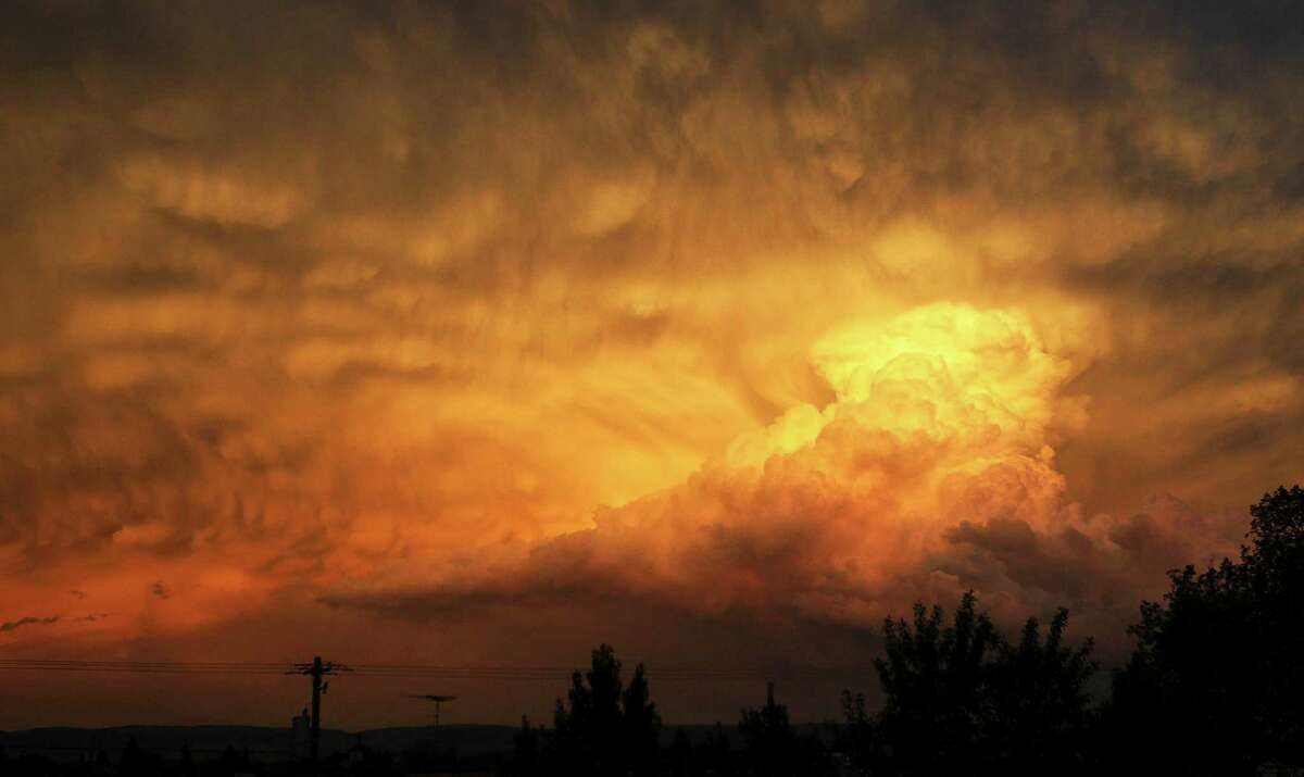 Nature paints an orange canvas as a thunderhead dissipates at sunset concluding a stormy Thursday in Laramie, Wyo.