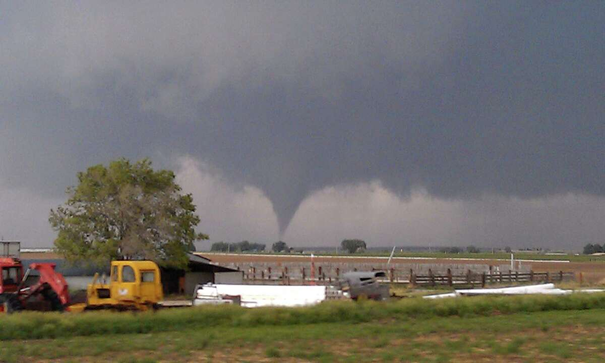 A Thursday photo provided by Andrew Kniss shows a funnel cloud, seen from Kniss's car on Highway 34, near Wheatland, Wyo. The rare quarter-mile-wide tornado cut a swath across mainly open country in southeastern Wyoming, damaging homes, derailing empty train cars and leaving one person with minor injuries, officials said. The twister was part of a powerful storm system that rolled through parts of Colorado and Wyoming on Thursday afternoon and evening, packing heavy rains, high winds and hail.