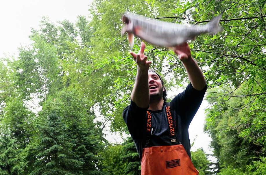 A Pike Place Market fishmonger catches a salmon as they have fun before the salmon toss event to feed the Woodland Park Zoo's 800-lb grizzly bear brothers. Photo: LINDSEY WASSON / SEATTLEPI.COM