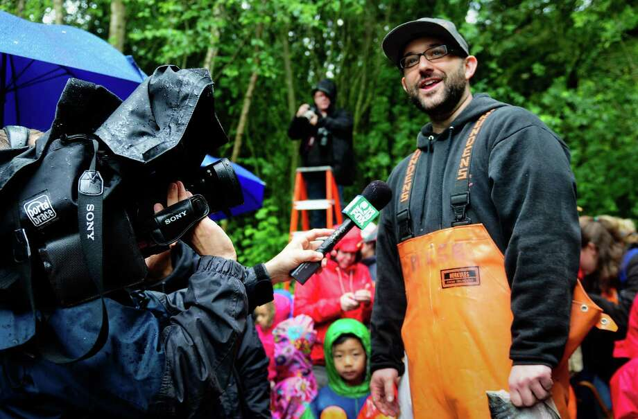 Pike Place Market fishmonger Ryan Reese holds a beheaded salmon as he is interviewed by the media during a salmon toss event to feed the Woodland Park Zoo's 800-lb grizzly bear brothers, Keema and Denali, on Thursday, June 7, 2012. The event was held to usher in the zoo's annual Bear Affair & Big Howl for Wolves event happening on June 9. Photo: LINDSEY WASSON / SEATTLEPI.COM
