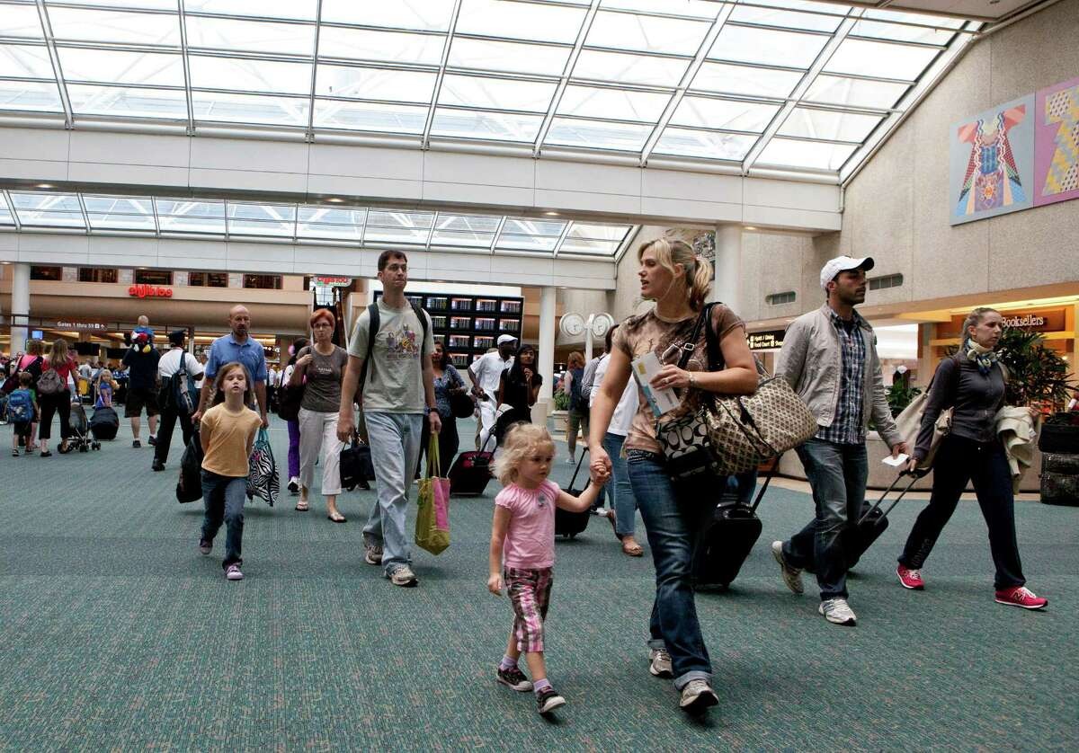 Travelers at Orlando International Airport head to the baggage claim. The average domestic round trip will be $431 this summer, but bargains can be found.