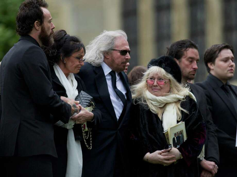 Barry Gibb, center left, and Robin Gibb's wife Dwina Gibb, center right, who holds an order of service, react at the graveside during the burial of Robin Gibb outside St Mary's Church in Thame, England, Friday, June 8, 2012. Robin Gibb a member of the iconic Bee Gees pop group died May 20, after a long battle with cancer.(AP Photo/Alastair Grant)(AP Photo/Alastair Grant) Photo: Alastair Grant, Associated Press / AP