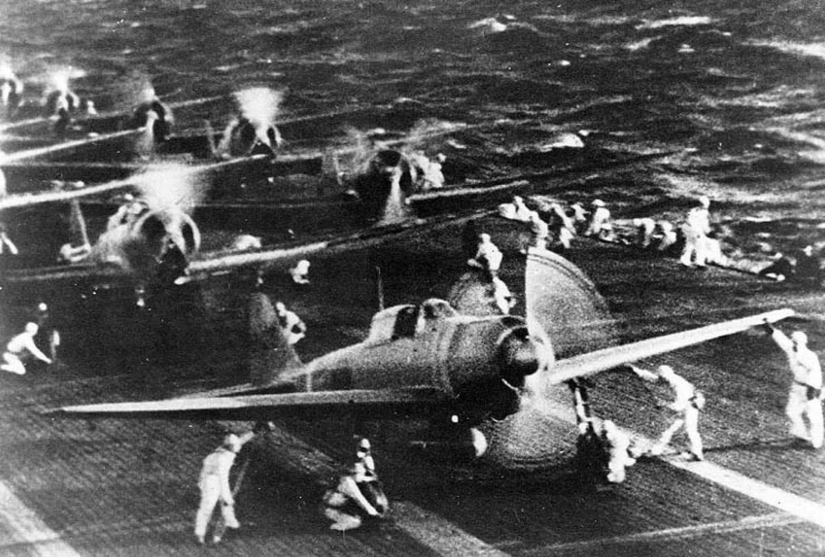 """Japanese naval aircraft prepare to take off from an aircraft carrier (reportedly Shokaku) to attack Pearl Harbor, Hawaii on the morning of Dec. 7, 1941. The plane in the foreground is a """"Zero"""" Fighter."""
