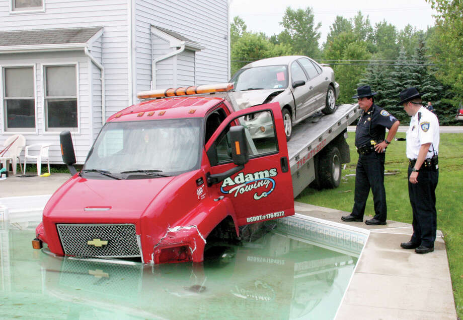 Talking on one cell phone and texting on another, the driver of this tow truck ended up in a swimming pool in Lockport, N.Y., in 2009. A reader has a suggestion for those who drive while using their cell phones. Photo: Associated Press File Photo / The Union-Sun & Journal