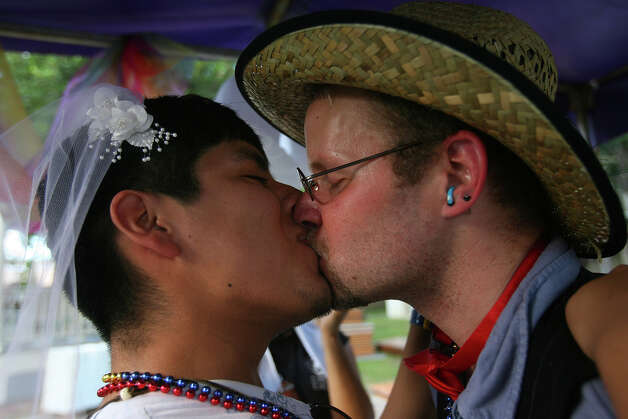 Rick Hernandez, left, and Jeremy James Lunceford kiss after a quick commitment ceremony at the non-profit Celebration Circle booth, a multi-faith community with a creative approach to spirituality, during PrideFest San Antonio 2010 at Hemisfair Park, Saturday, June 12, 2010. (Jennifer Whitney/ special to the San Antonio Express-News) Photo: Jennifer Whitney, Special To The Express-News / special to the San Antonio Express-News