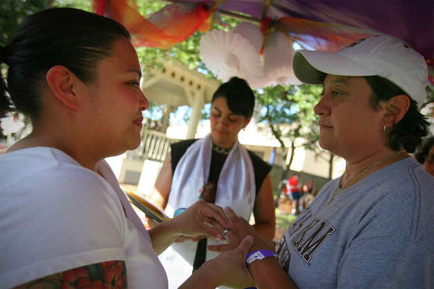 Illiana (cq) Galvan, left, and Cecelia Gomez exchange rings during a commitment ceremony performed by Jai Medina, center, community director for the non-profit Celebration Circle, a multi-faith community with a creative approach to spirituality, during PrideFest San Antonio 2010 at Hemisfair Park, Saturday, June 12, 2010. (Jennifer Whitney/ special to the San Antonio Express-News) Photo: Jennifer Whitney, Special To The Express-News / special to the San Antonio Express-News