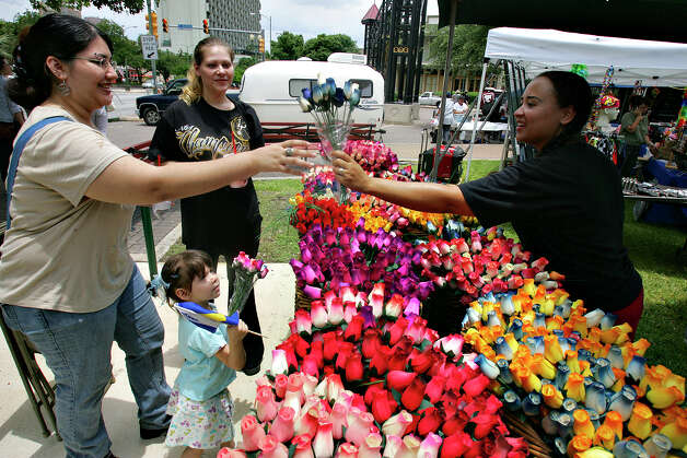 METRO - Sandra from House of Rings, right, sells artificial flowers to Helen Salazar, left, her sister Stephanie Aparicio, and Stephanie's daughter, Trinity Bravo, during Pridefest Saturday, June 16, 2007 at Hemisfair Park. BAHRAM MARK SOBHANI/STAFF (NOTE: SANDRA DID NOT WANT TO GIVE HER LAST NAME.) Photo: BAHRAM MARK SOBHANI, SAN ANTONIO EXPRESS NEWS / SAN ANTONIO EXPRESS NEWS