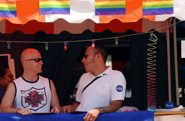 METRO GAY PRIDE FESTIVAL 6/20/04  Brian Asher, left, and Julian Ledezma enjoy conversation while working the Citibank booth during PrideFest, San Antonio's gay pride festival at Sunset Station on Sunday, June 20, 2004. ( JERRY LARA STAFF ) Photo: JERRY LARA, SAN ANTONIO EXPRESS-NEWS / SAN ANTONIO EXPRESS-NEWS