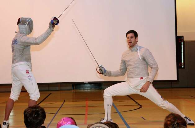 Olympic fencer and silver medalist Tim Morehouse, right, puts on