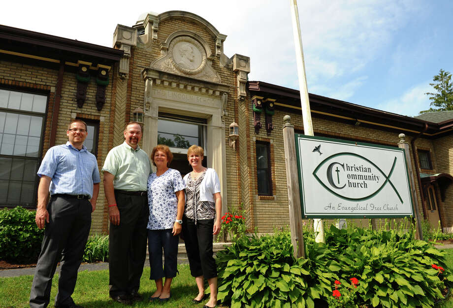 Christian Community Church Pastor Walt Mayhew and his wife Linda, stand with Walnut Hill Community Church Regional Development Pastor Adam DePasquale, left, and WHCC Communications Director Lisa Siedlecki, right, in front of the church, which is the former Lincoln School building in Derby, Conn. on Friday June 8, 2012.The two chuch will merge and CCC will be disolved. Photo: Christian Abraham / Connecticut Post