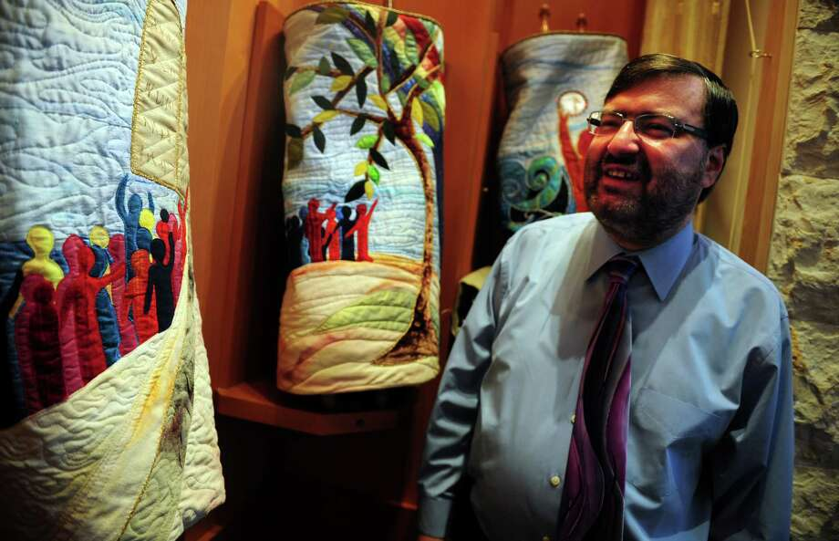 Rabbi Colin Brodie of Congregation B'nai Torah of Trumbull looks at the synagogue's collection of Torahs Thursday June, 7, 2012. Photo: Autumn Driscoll / Connecticut Post