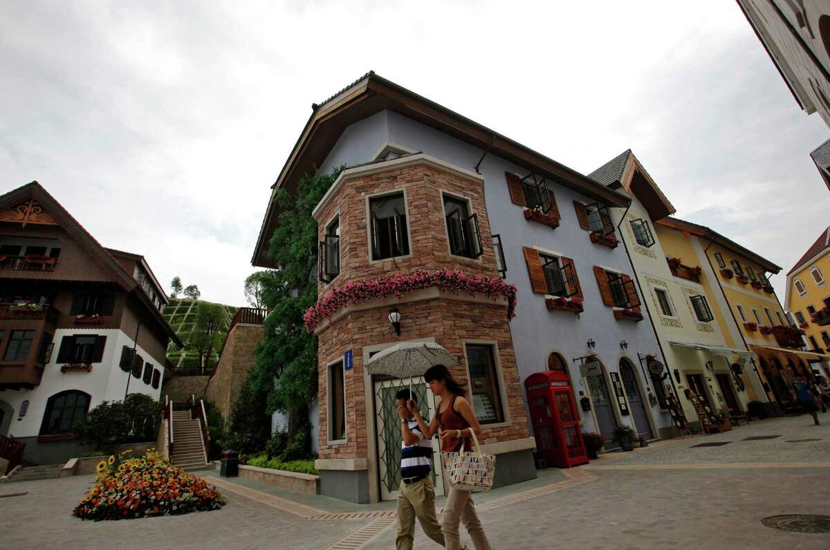 Chinese visitors walk by European-style houses in Hallstatt See, a replica of the Austrian town of Hallstatt, in Boluo county, Huizhou city, south China's Guangdong province on Saturday, June 2, 2012.